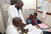 Two medical personnel review a chart while a mother and her child look on.
