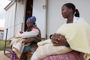 Photo of two women holding their babies outside a building