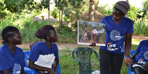 A DREAMS team member shares information with other women.