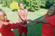 Photo of three women wearing red dresses holding hands in a circle