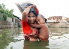 A mother carries her child in one hand and a packet of collected food in the other down a flooded road on the outskirts of Dhaka