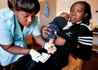 A nurse takes dried blood spot samples from an infant to test for HIV in a maternal and child health ward in a Malawi clinic.