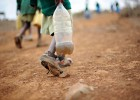 A Kenyan school boy wearing worn out shoes carries a plastic bottle filled with river water as he heads back to school.
