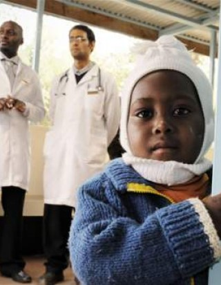 A child peers around the corner in the waiting room of the HIV Comprehensive Care Clinic of Meru District Hospital in Kenya