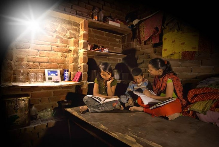 Picture of household reading at night thanks to Simpa Networks' Lights for Education program