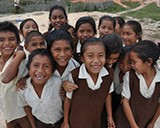 A group of children laugh and smile in a schoolyard in Guyana. © 2014 Lorine Ghabranious/MSH, Courtesy of Photoshare