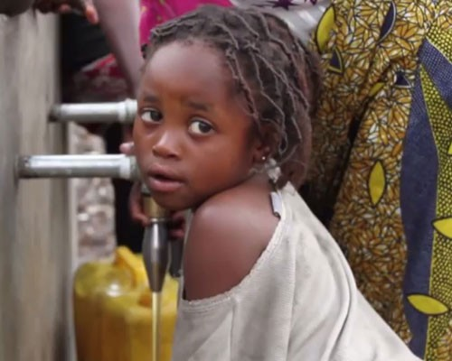 A young girl uses a tap stand to get water for her family.
