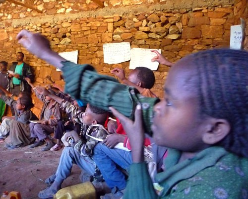 Third graders raise their hands at a USAID-sponsored Alternative Basic Education Center providing accessible schooling for young