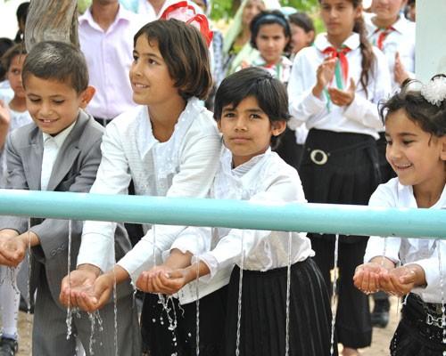 Children experience clean water running through their hands.