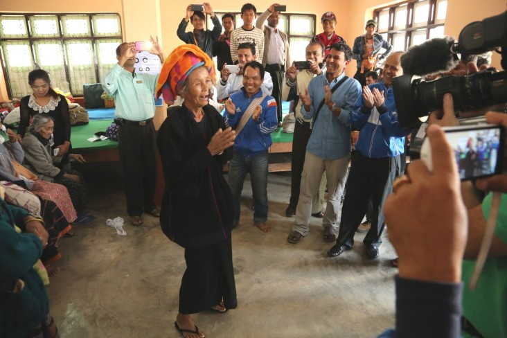 A woman dances after removing her bandages following cataract surgery.
