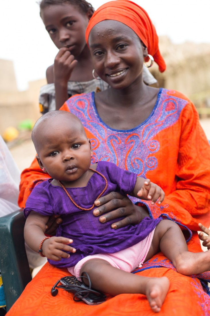 A woman holds her child during a mother-to-mother meeting in the village of Doumga Rindiao, Senegal, September 2012.