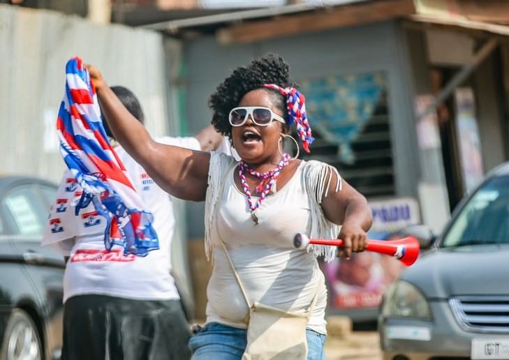 A jubilant Ghanaian woman wearing the colors of the victorious New Patriotic Party celebrated in the street after the election results were announced.