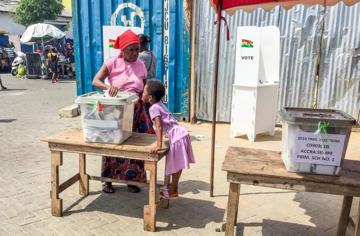 A child watches as her mother puts her ballot in the secured ballot box.