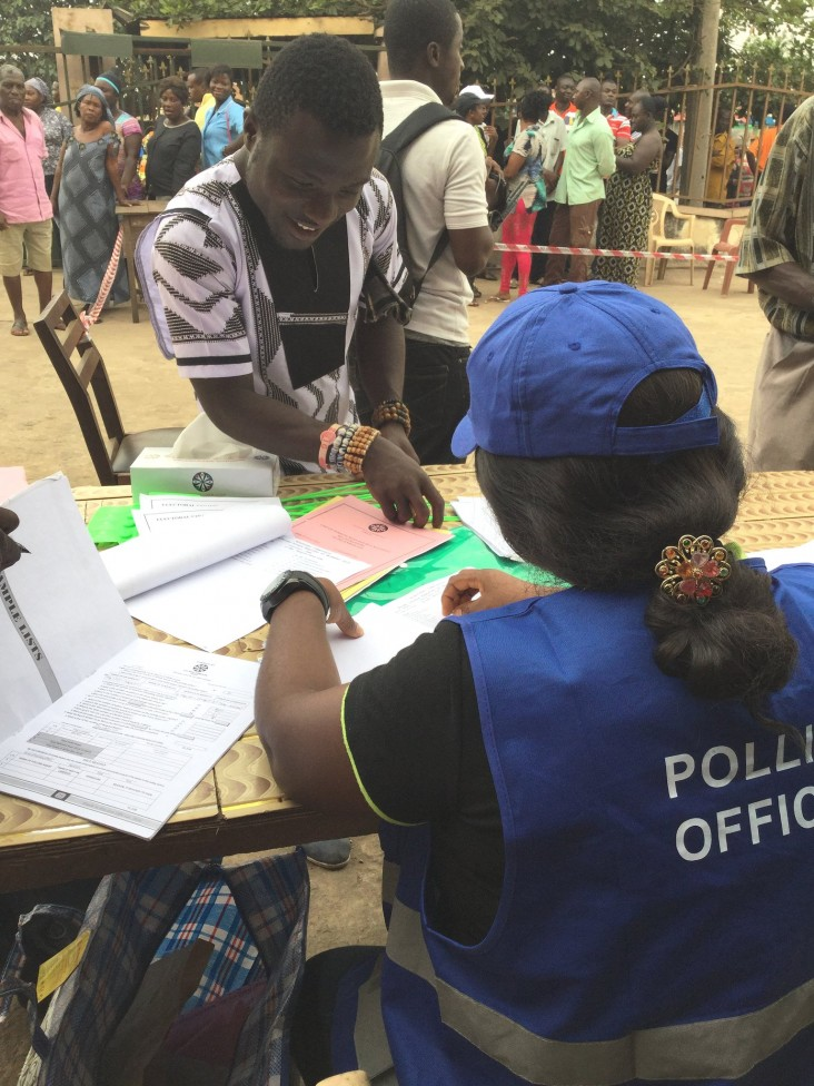 A voter is helped by an Electoral Commission polling official. USAID helped prepare the Electoral Commission to administer the election.
