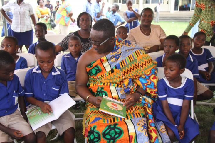 Chief Osabarima Ansah Sasraku II of Mamfe village interacts with children during the reading festival in Koforidua.