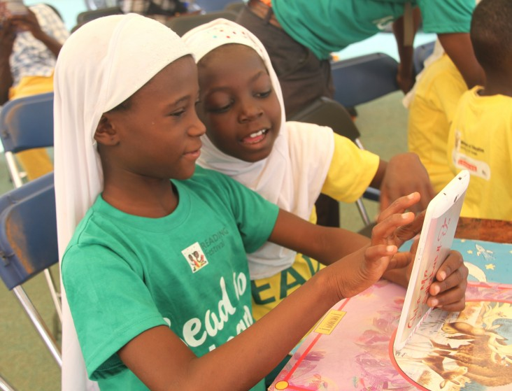 """Pupils use a tablet in the """"digital zone"""" during the reading festival in Tamale."""
