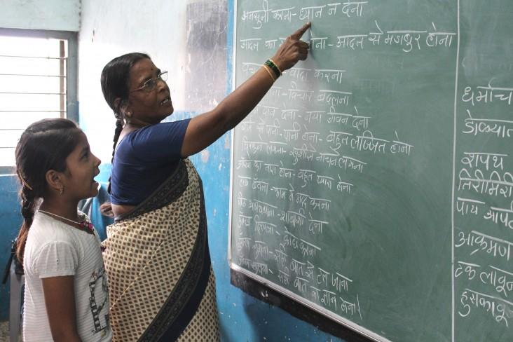 "Schoolteacher Jayshree Kopershinde helps her ""chatterbox"" student, Swati, read sentences."