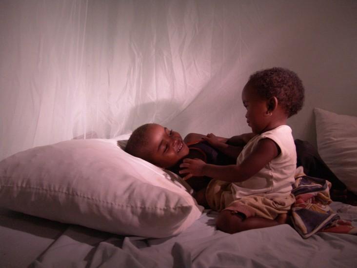 Two children sit under a bednet