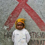 A young boy standing in front of a red ribbon painted on the wall.