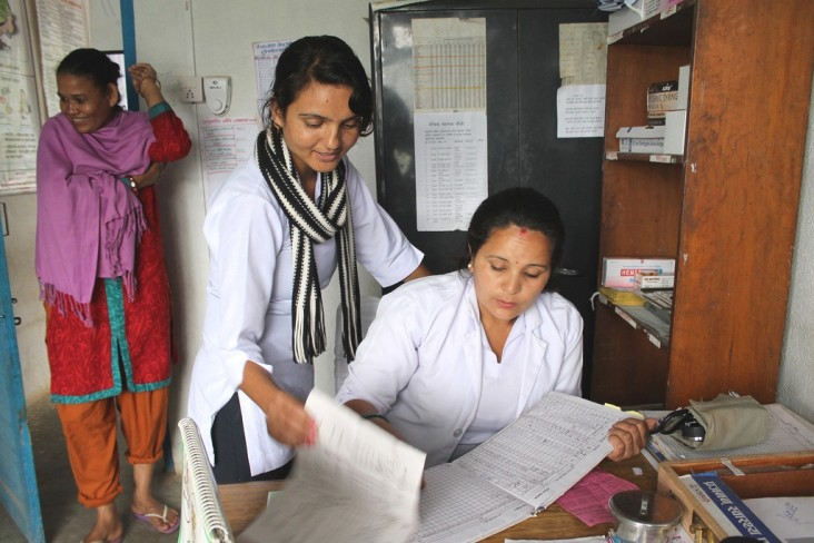 Staff at a rural health clinic consult as a patient waits her turn in rural Nepal.