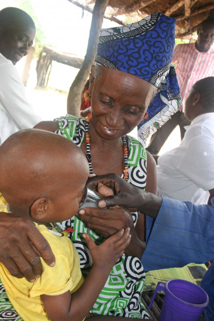 Rougui Diallo holds her son as he drinks malaria prevention medicine.