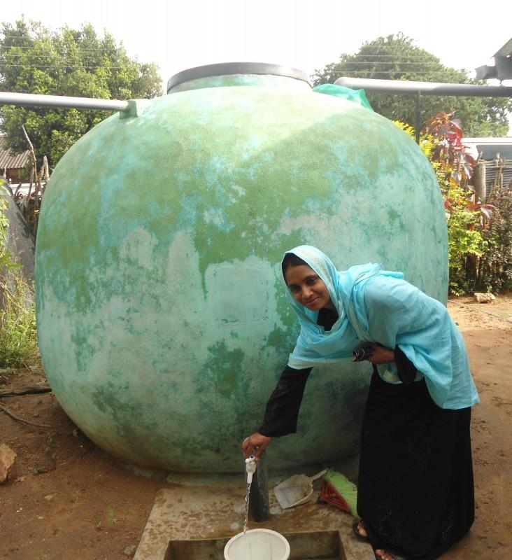 Safra Siddiq in front of the rainwater harvesting system