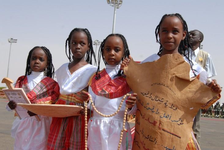 Four girls hold a hand-written sign
