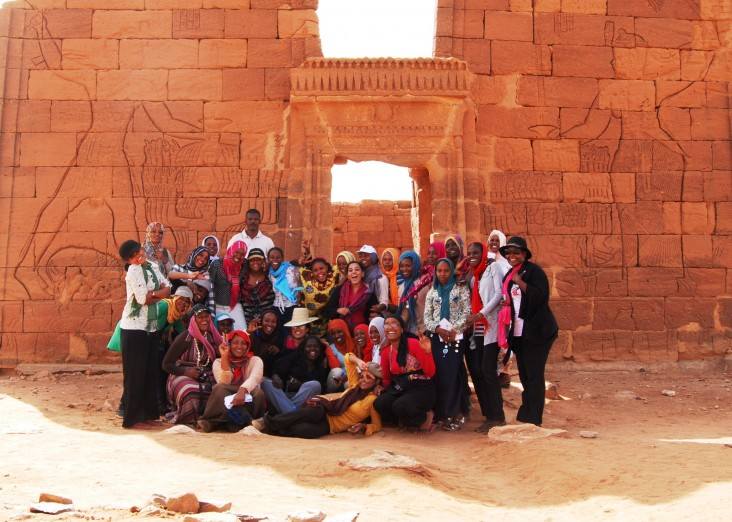 A group of young women stand in front of an ancient temple.