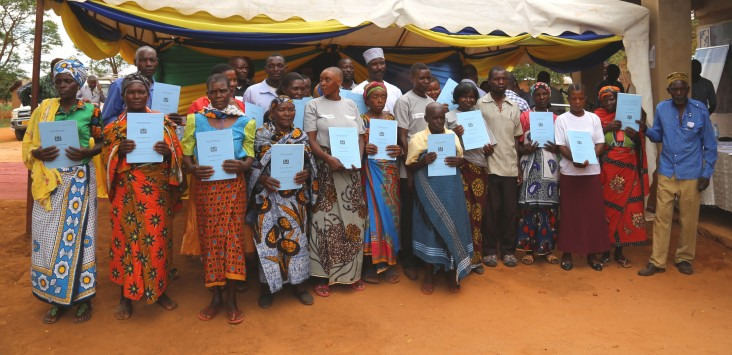 Landholders in Kinywang'anga village hold up their newly received certificates of customary right of occupancy.