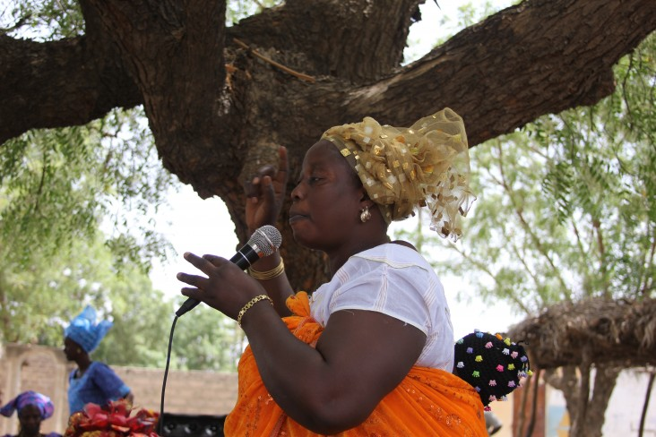 A beneficiary of USAID Women's Empowerment and Civic Journalism project addressing a community in rural Senegal