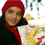 A young woman holds up AIDS Day promotional materials