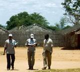Three men in a dusty village