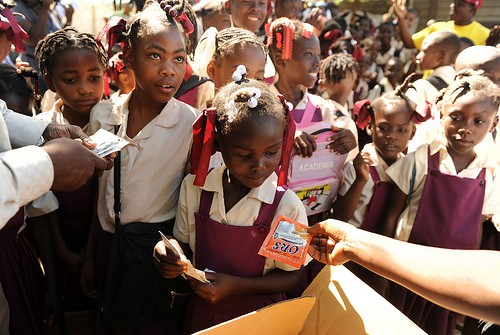 Schoolchildren pick up sachets of oral rehydration salts distributed by USAID/OFDA partner Mercy Corps.
