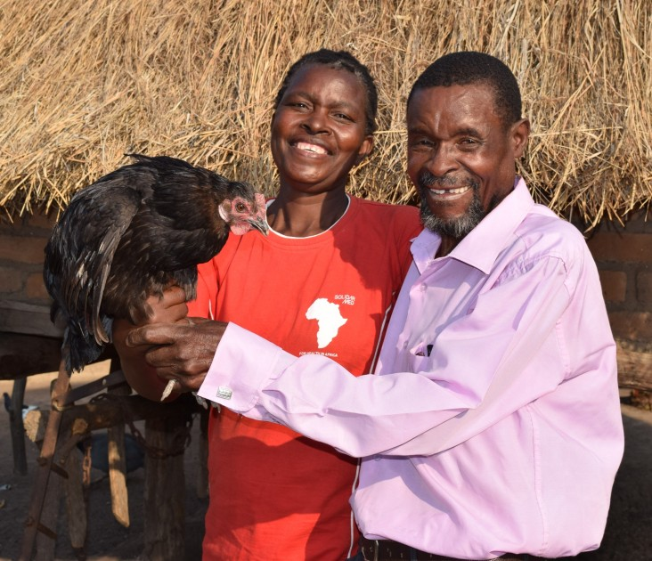 Gosha Zimhatye and his wife show off a prize hen from their poultry project.