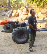 """A Cambodian farmer stands next to a two-wheeled """"Iron Buffalo"""" tractor."""