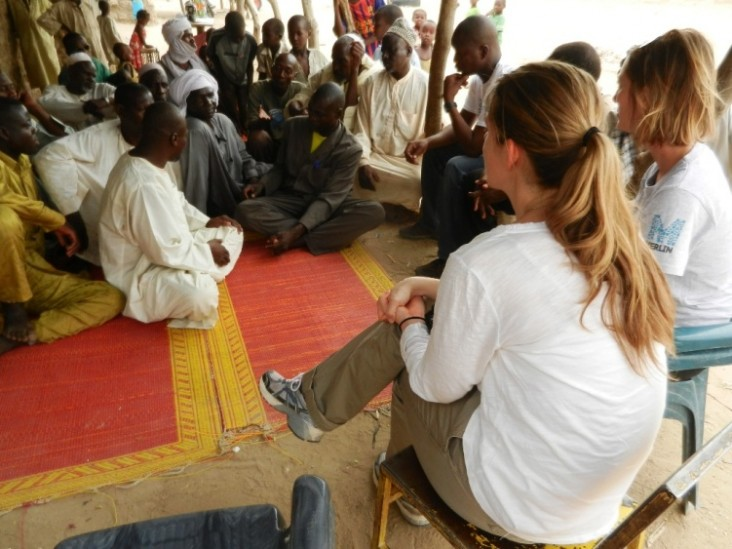 A USAID/OFDA staff member (foreground) meets with a men's group in Chad while conducting a field visit