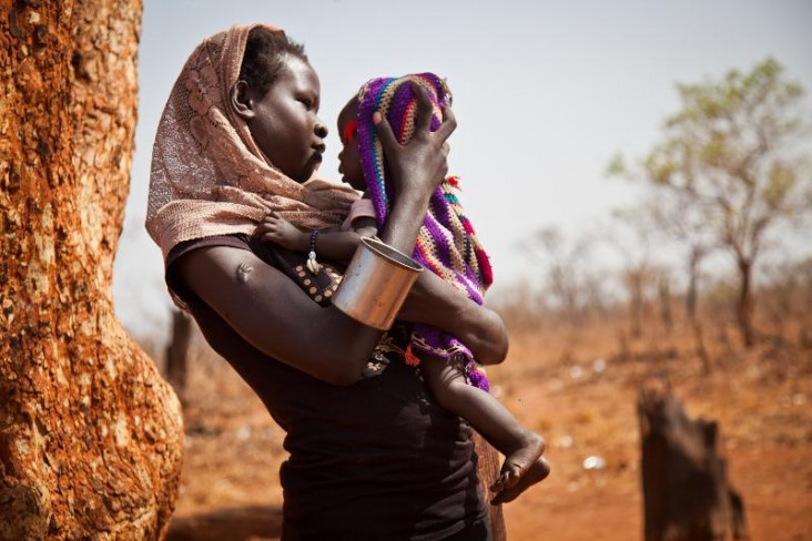 A woman and her child from the Nuba Mountains in Sudan wait outside of the Yida refugee camp registration center in South Sudan