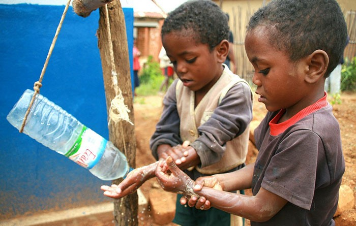 """Children in Madagascar use the low cost, low tech, water-conserving """"tippy tap"""" to wash their hands"""