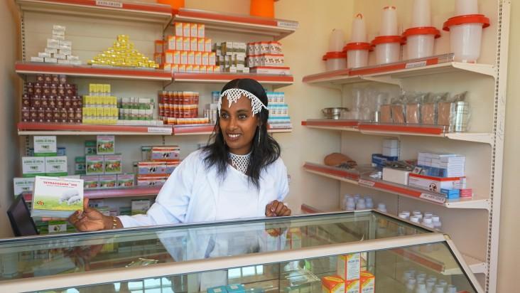 Angatu Ayansa, an employee of the Bako Farm Service Center, helps a customer in selecting merchandise.