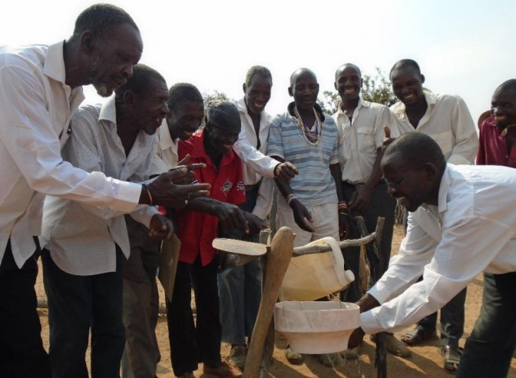 The men of the Asisizaneni Community Health Club demonstrate how to use a tippy tap for hand washing.