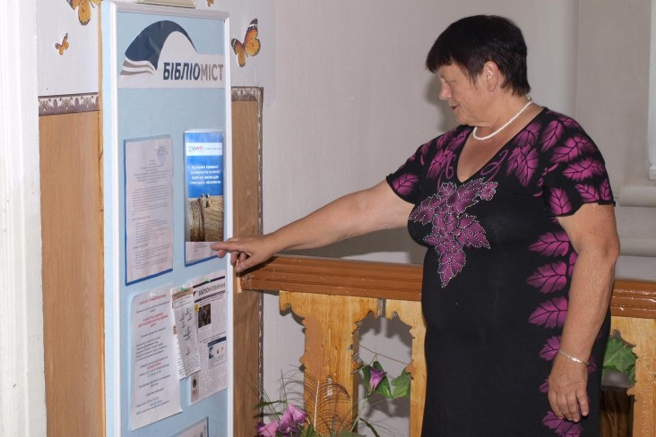 Vira Ovcharenko reads a poster in the USAID-supported Law Center that provides procedures for land rights registration.