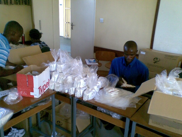 Staff re-packaging the female condoms in packs of 20 pieces.