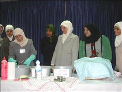 Basma demonstrates infection prevention and quality control to her colleagues.