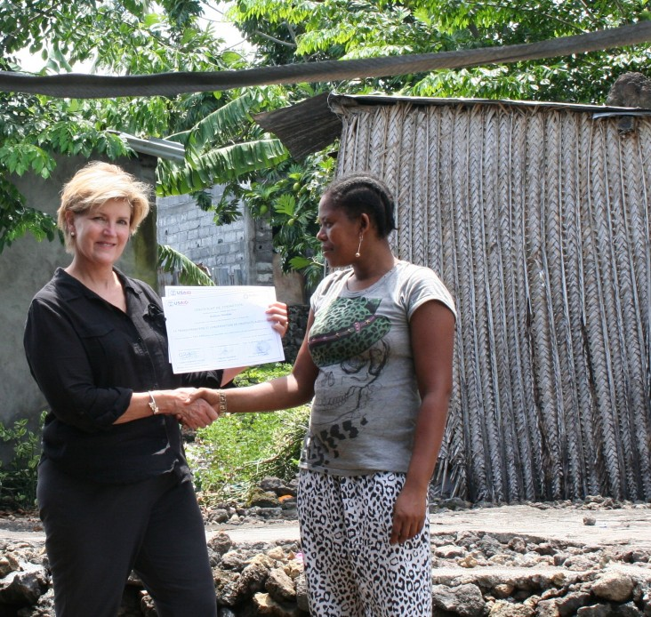 USAID Mission Director Susan Sawhill Riley presents a training certificate to Radiata Ibrahim
