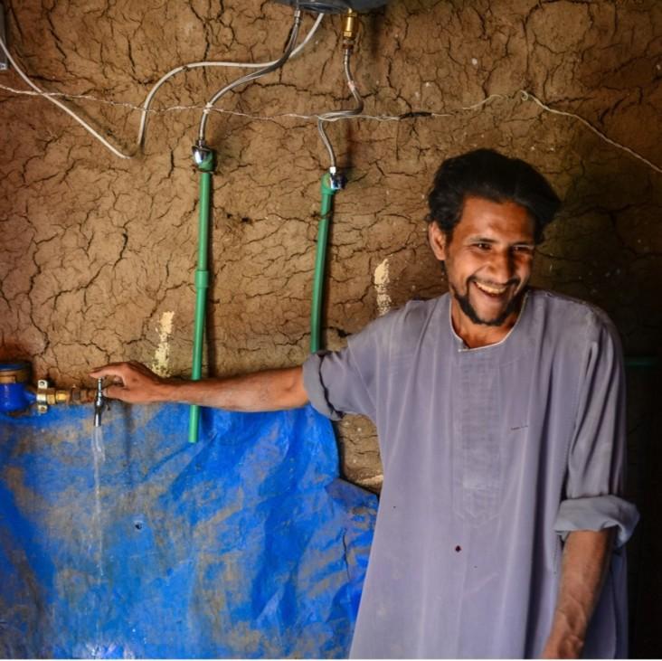 man at water faucet