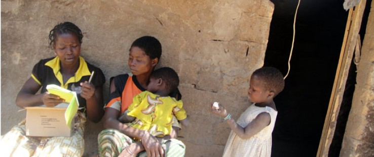 Community health worker Rosalina Casimiro, far left, meets with a family in Nampula province, Mozambique, to distribute kits for