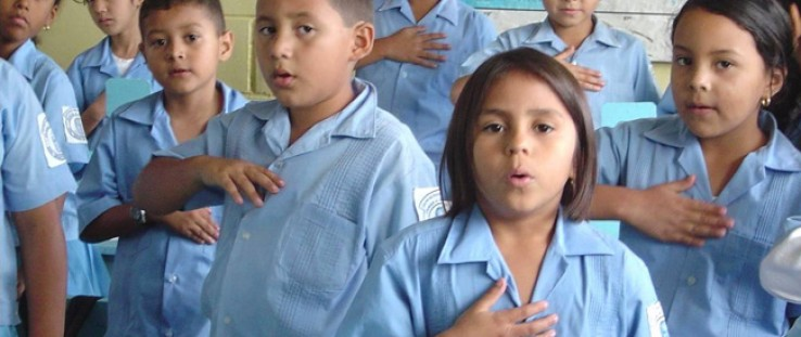 Children involved in a USAID democracy program sing the Honduras national anthem. The Agency has supported democracy programs in