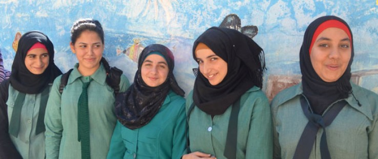 Girls in Jerash pose in front of their school's storage tank that is painted to look like an aquarium.