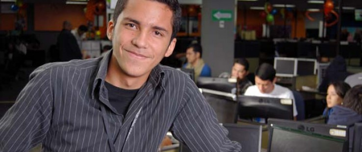 Nineteen-year-old Hugo Ruiz poses for a photo at Transactel, where he has worked as an IT customer support representative in the