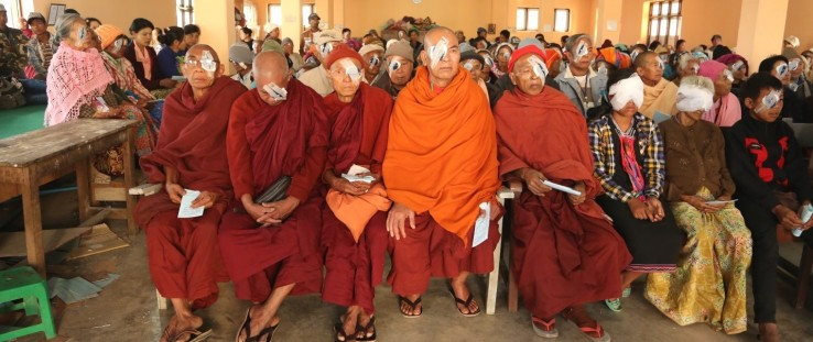 Monks sit among a group of people waiting to remove their bandages following cataract surgery.
